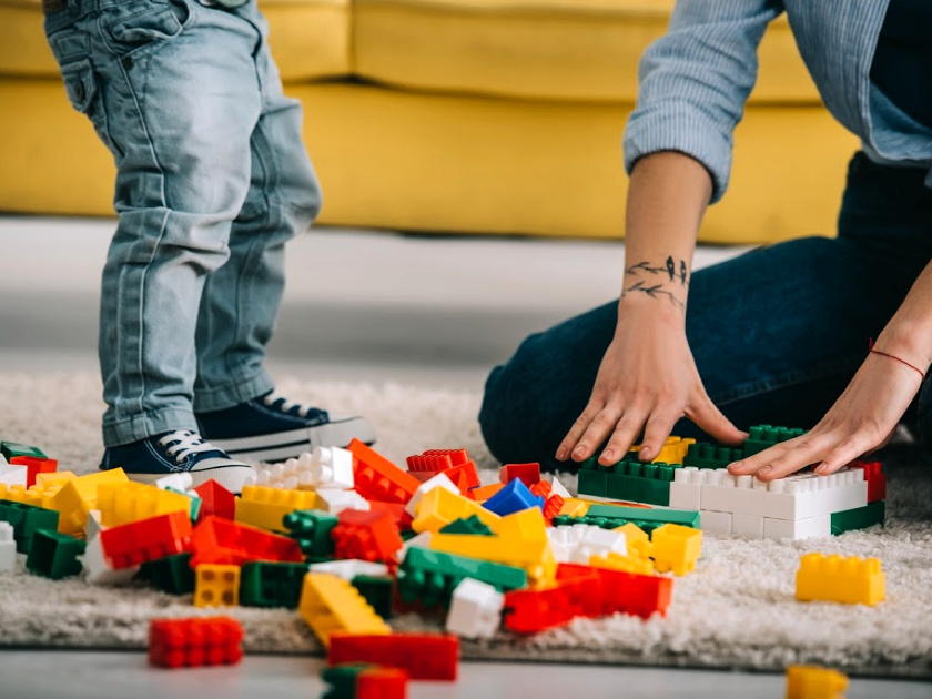mom and child playing with legos on the floor