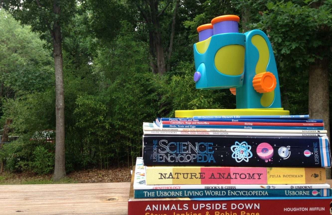 stack of science books for unschooling science sitting on a table, with a toy microscope on top.