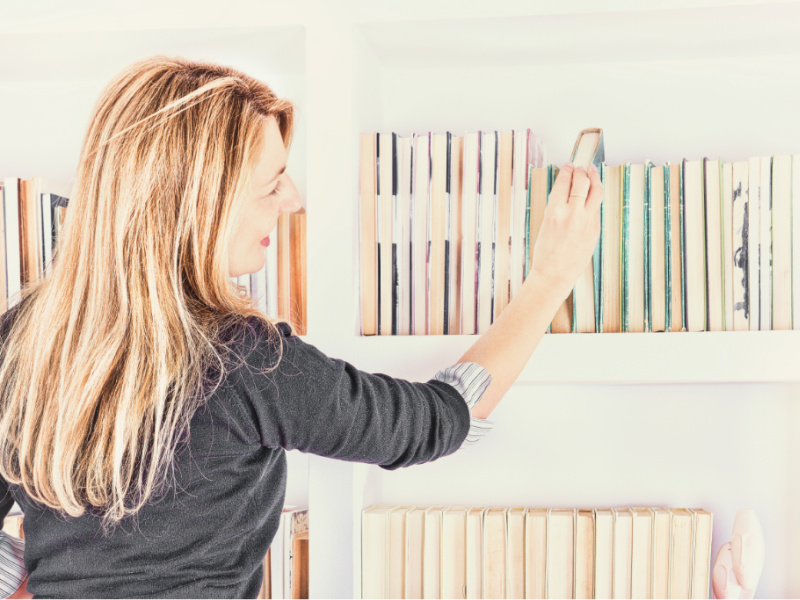 woman selecting books for homeschool year