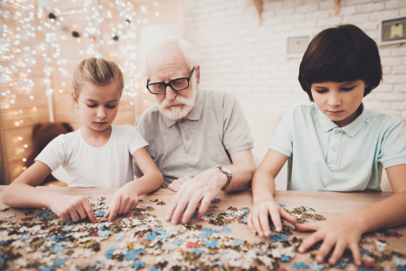 grandpa and children doing a puzzle at Christmas