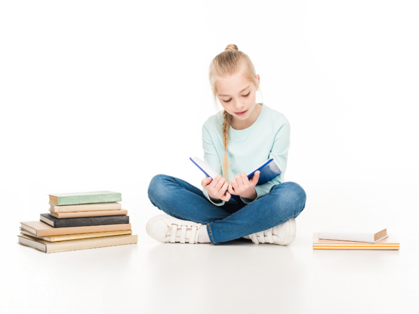 girl reading books with stacks of books beside her
