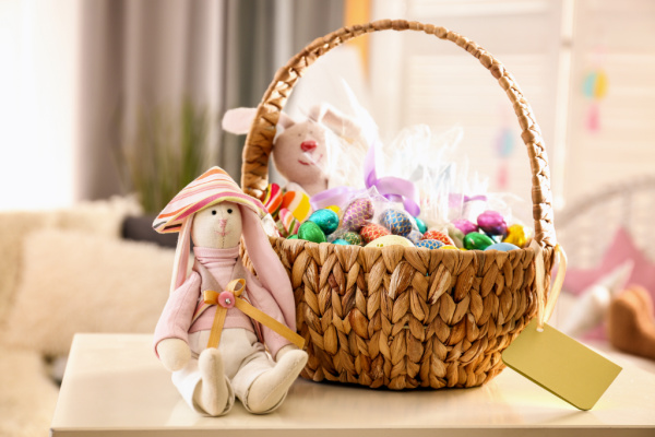 Easter basket for kids with chocolate eggs and a bunny stuffed animal sitting next to it