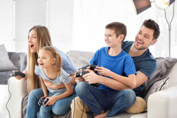 mom and dad playing video games with two kids, all sitting together on couch
