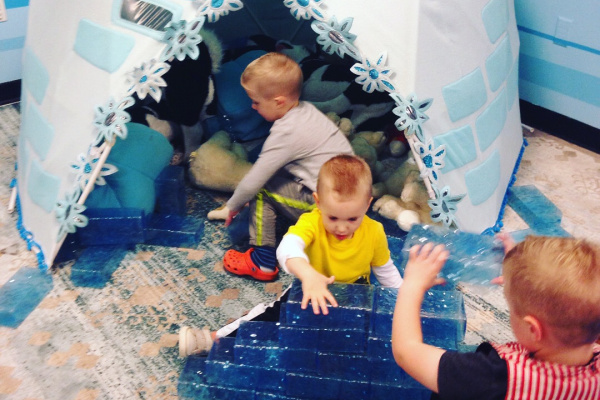 children visiting science museum, playing in igloo and building with pretend ice bricks