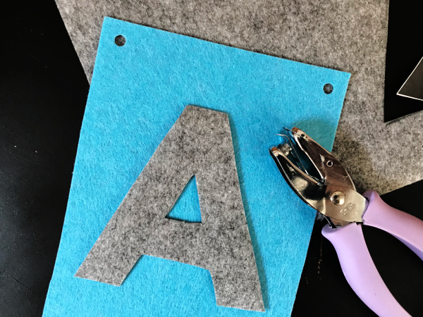 hole punch next to hole punched felt alphabet banner piece