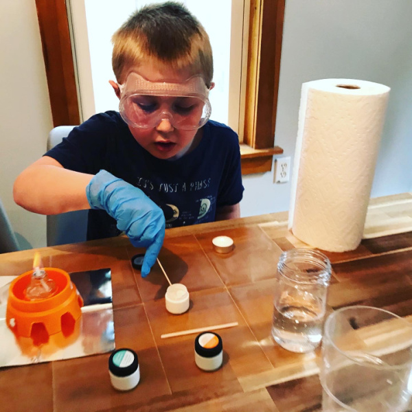 homeschooled child doing science experiment with fire and chemicals