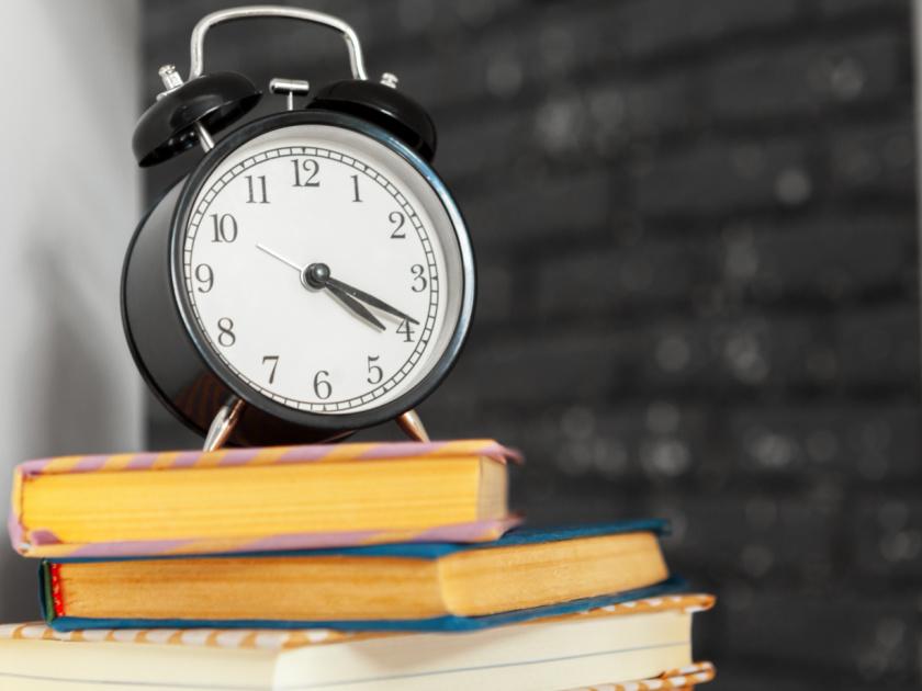 alarm clock on top of homeschool books, representing homeschool schedule