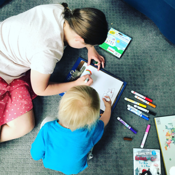 homeschooled sisters - one much older than the 2-year-old - drawing on the floor together