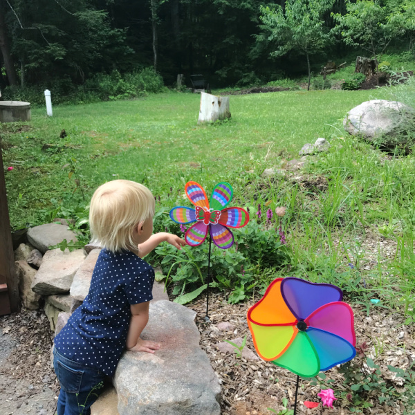 homeschooling two-year-old blond child looking at colorful spinner in a garden
