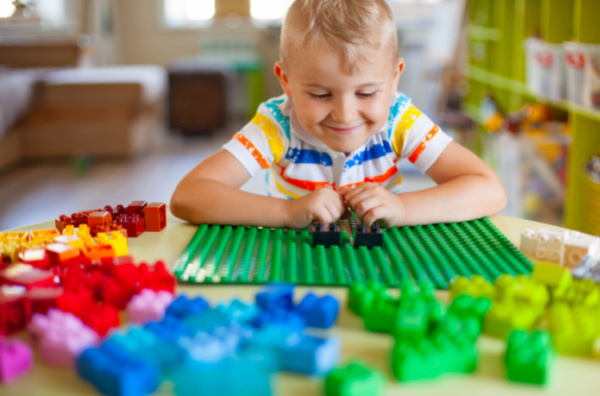 little boy playing with colorful duplo blocks
