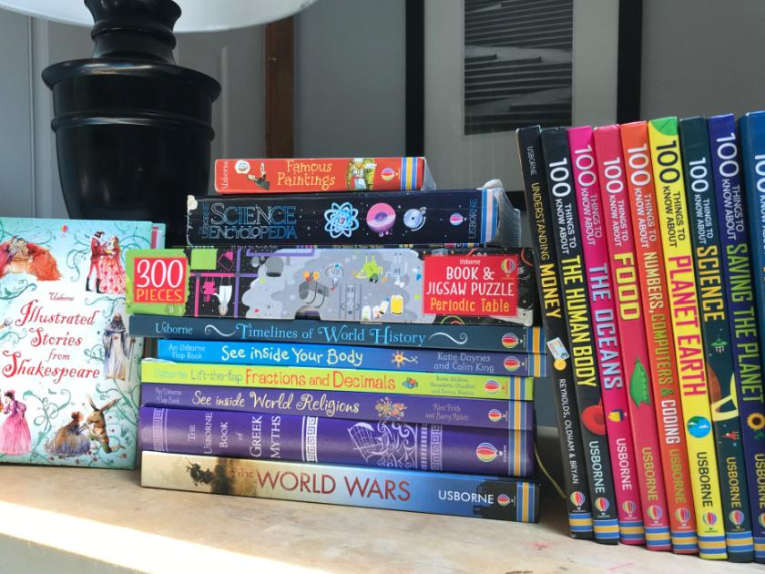 usborne homeschool books on table next to lamp