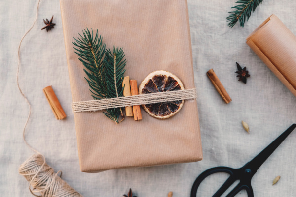 Minimalist gift wrapping with natual decorations - fir branches, cinnamon sticks