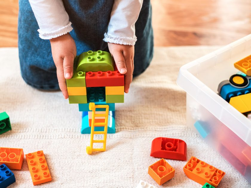 Little girl playing with her colorful blocks on the floor at home.