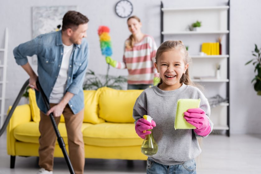 homeschool family - mom, dad, and child - cleaning the house together
