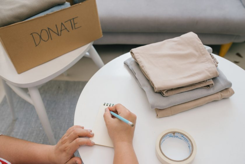 homeschool mom working on decluttering, sitting at table with list and donation box